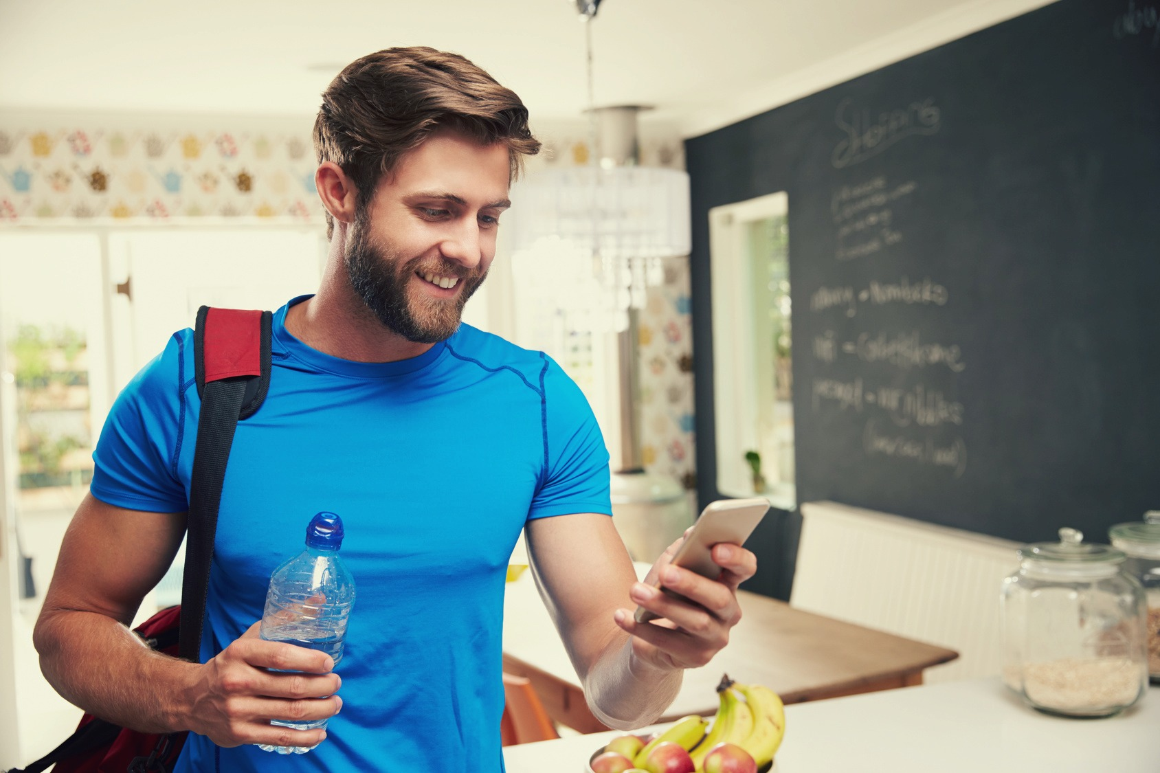 Man Wearing Gym Clothing Looking At Mobile Phone